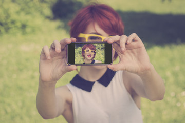 Phone Camera. Cute hipster girl taking a photo of herself