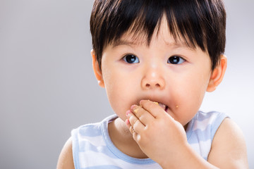 Asian baby boy eat cookie close up