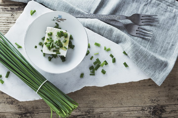 Cheese with chives on wooden background