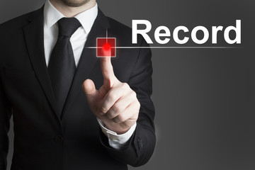 businessman in black suit pushing red touchscreen button record