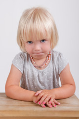 Portrait of cute little girl sitting at desk thinking