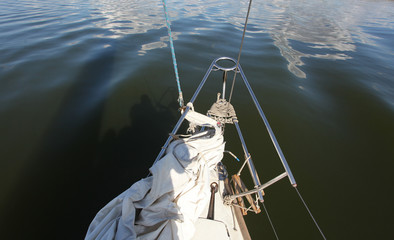 front of the yacht with a deflated sails on lake background