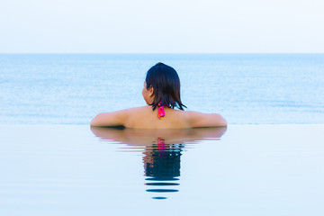 Woman relaxing infinity swimming pool