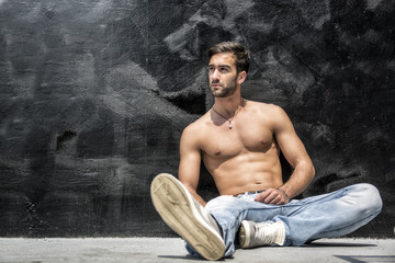 Handsome bearded shirtless young man sitting