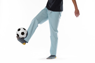 Young man dressed in pyjama and football ball