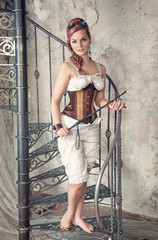 Beautiful steampunk woman with whip on the stairway