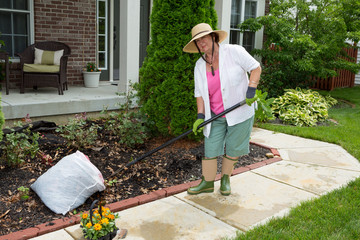 Old lady at work in the garden cleaning flowerbeds
