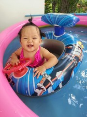 Baby in small swimming pool. Smile and happy