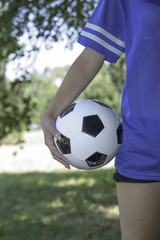 backside female holding a soccer ball