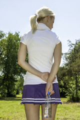 beautiful back of athletic woman that holds bottle of water