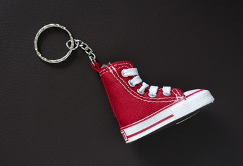 Key chain with mini basketball shoe on leather pad.