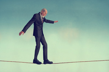 senior man walking a tightrope