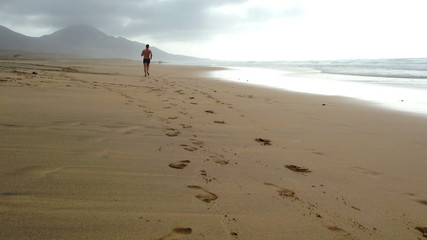 Man jogging on the Cofete beach, Fuerteventura, Canary Island