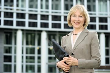 Lächelnde Geschäftsfrau vor einem Bürogebäude