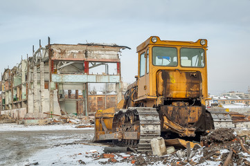 Bulldozer in front of old industrial building