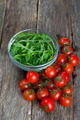 fresh rucola and cherry tomatoes on wooden surface