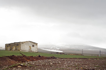 Deserted house and foggy mountains, Javakheti Plateau, Georgia
