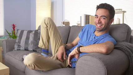 Happy Mexican man resting on couch