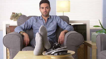 Handsome Latino sitting on couch looking at camera