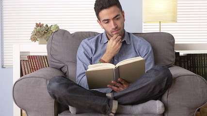 Mexican man reading a book at home