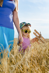 Little girl walking in a wheat field with mother