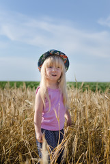 Little girl walking in a wheat field