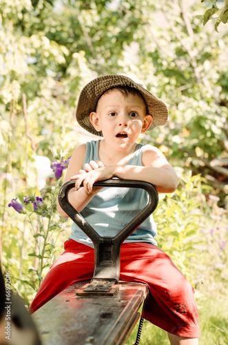Cute little country boy sitting in a garden