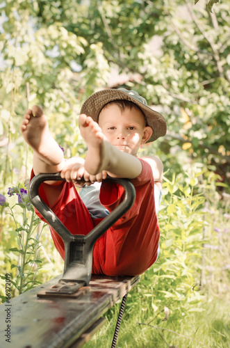 Cute little country boy sitting in a garden