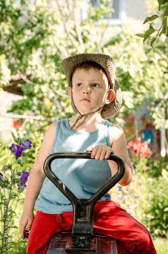 Thoughtful young boy sitting in a country garden