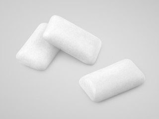 Three pieces of white chewing gums on gray with clipping path