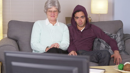 Grandma watching TV with bored Hispanic grandson
