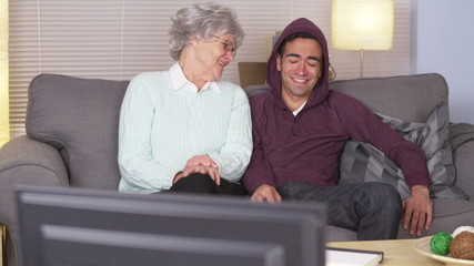 Elderly woman watching TV with Mexican man