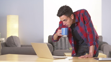 Hispanic man working on laptop and drinking coffee