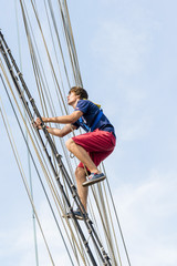 Young sailor climbing on mast of tall ship.