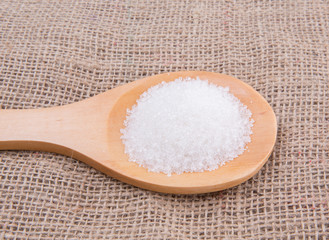 White refine sugar in wooden spoon on gunny sack background