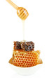 Honey dripping on honeycombs isolated on white