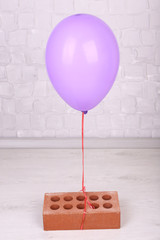 Color balloon with brick on grey wall background