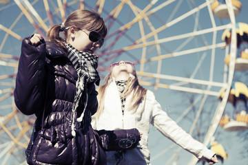 Teenage girls against a ferris wheel