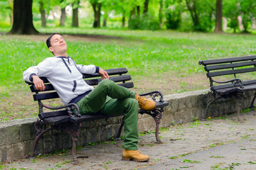 Young man daydreaming on the bench in the park