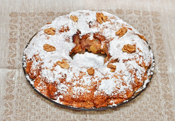 Round homemade biscuit cake on plate and napkin