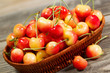 Freshly Picked Golden Rainier Cherries in Basket on Rustic Wood