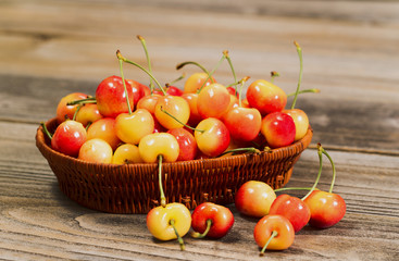 Juicy Golden Rainier Cherries in Basket on Rustic Wood