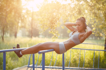beautiful fitness woman doing exercise on bars sunny outdoor