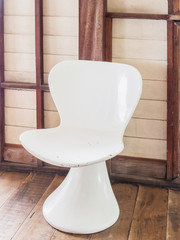 Retro white chair on wooden floor