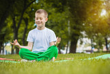 happy kid is doing exercises in the park