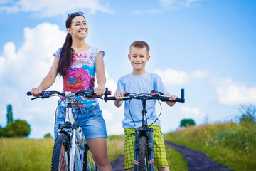 happy mother and son riding bicycle in the field