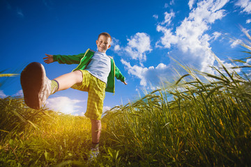 Running little happy boy in the  meadow weat field