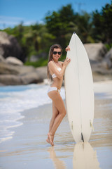 A beautiful young woman in a bikini with surfboard