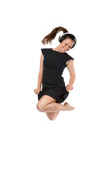 girl in a dress with headphones jumping
