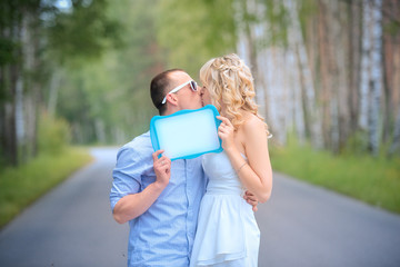Groom kissing bride holding nameplate